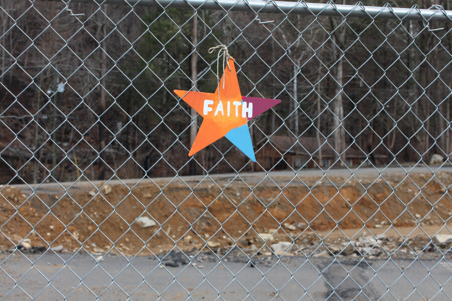 FAITH sign hanging on fence at building site